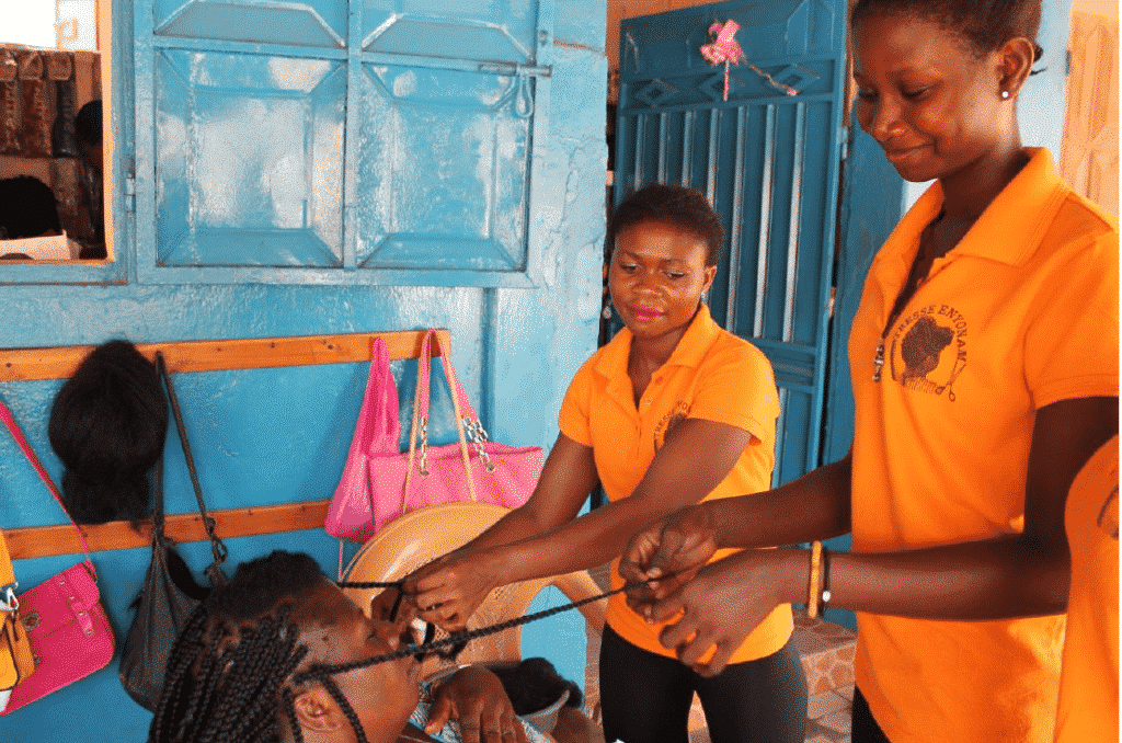 Photo of two girls in braiding another woman's hair